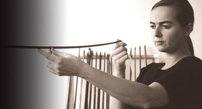 Bogenbau: am rechten Bildrand die Bogenbauerin Martha Breit, einen Geigenbogen in Kopfhöhe und Längsrichtung haltend, bei der visuellen Kontrolle der Krümmung.